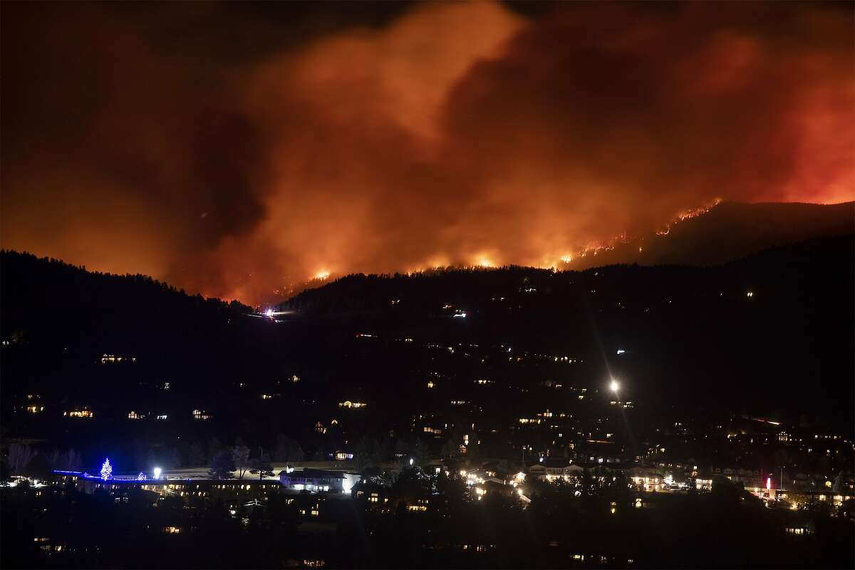 Flames from the Cameron Peak Fire, the largest wildfire in Colorado history, burn trees along a ridge outside Estes Park, Colo., Friday, Oct. 16, 2020. (Bethany Baker/Fort Collins Coloradoan via AP)