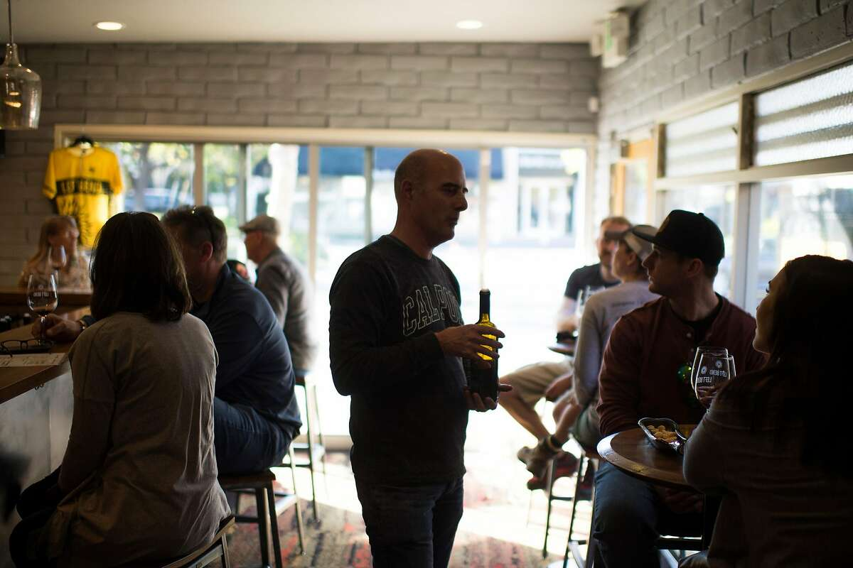 Winemaker Gary Robinson (center) pours wine for customers at Left Bend Winery in Los Gatos, Calif.