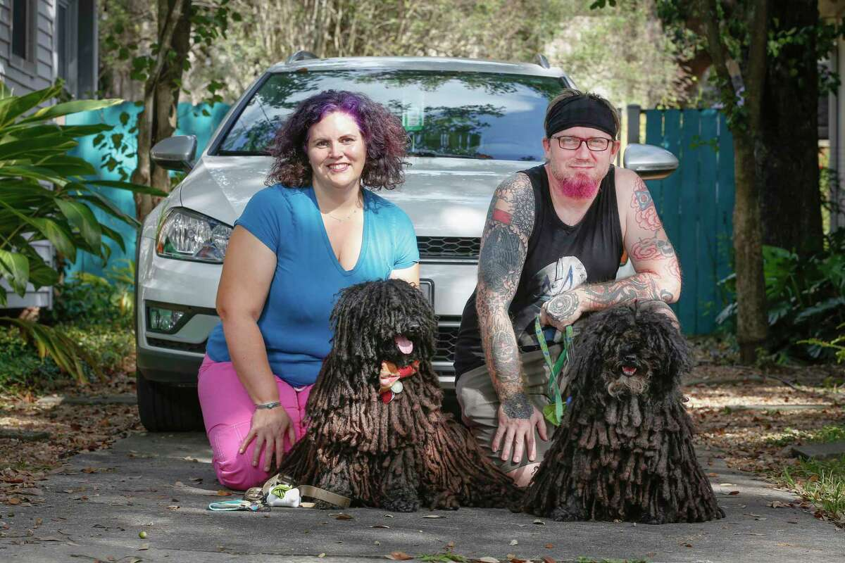 Christina Solis (left), her husband Graham Gaskill, and their Hungarian sheepdogs Fusilli and Celosa photographed in front of their Volkswagen Thursday, Oct. 22, 2020, in Houston. For Thanksgiving, the four of them plan to travel to Christina's parents' place in Taos.