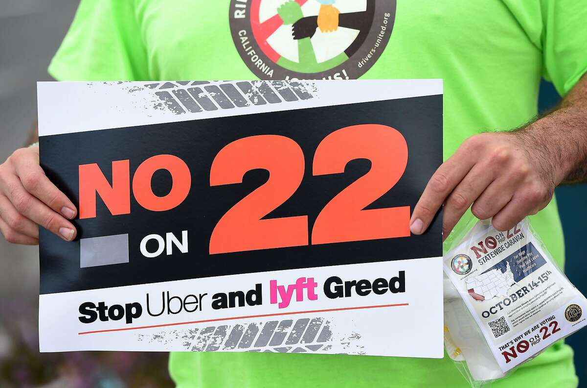 A ride-hail driver holds up a sign supporting a no vote on Proposition 22 in Oakland, Calif., on Oct. 9, 2020. Ahead of a referendum that could upend the whole gig economy, Uber driver Karim Benkanoun says his relationship with the gig-economy giant must stop being a one-way street.