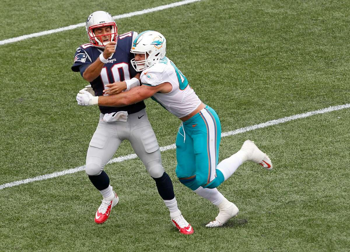 Miami Dolphins linebacker Kiko Alonso, right, hits New England Patriots quarterback Jimmy Garoppolo (10) after he threw a pass during the first half of an NFL football game Sunday, Sept. 18, 2016, in Foxborough, Mass. Garoppolo was injured on the play and did not return to the game. (AP Photo/Stew Milne)
