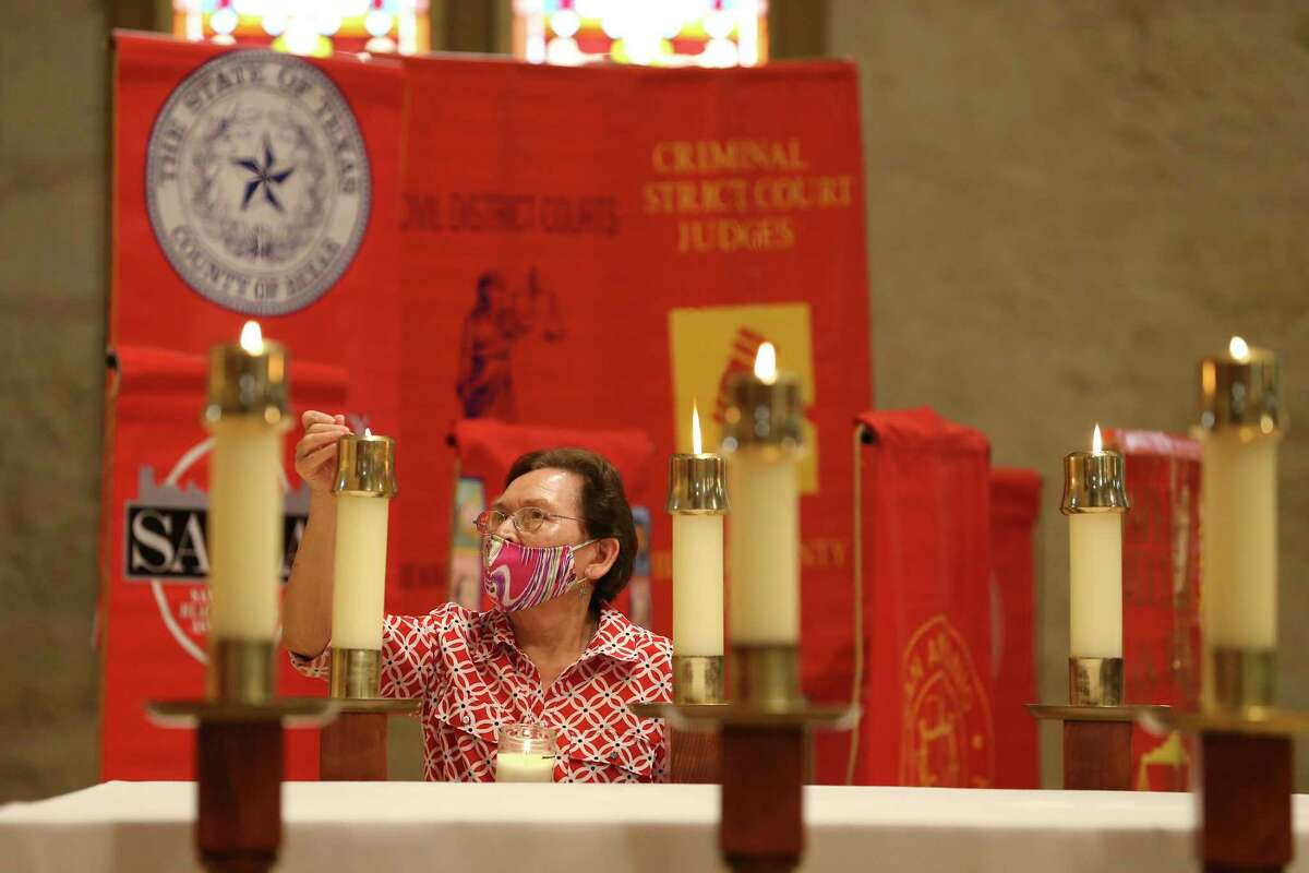 Maria Tovar lights candles on the altar at San Fernando Cathedral before the start of the Red Mass, Thursday, held each year to bless and guide the administration of justice. It is sponsored by the St. Mary's University School of Law.