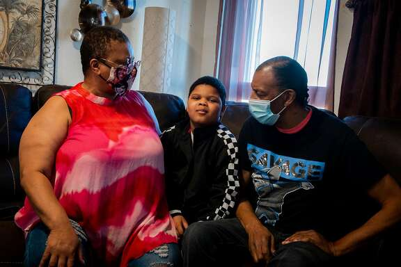 Joan Thomas who is raising her 9-year-old grandson , Royal, who has special needs and cannot access everything he needs including therapy on Zoom, poses for a portrait with Royal and her husband on October 21, 2020 in San Francisco, Calif.
