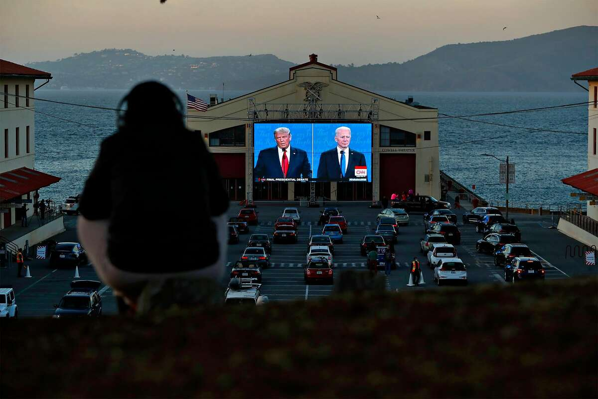 People watch the final US Presidential debate between President Donald J. Trump and former Vice President Joe Biden on a video screen at Fort Mason in San Francisco, Calif., on Thursday, October 22, 2020. The debate watch party was organized by businessman Manny Yekutiel.