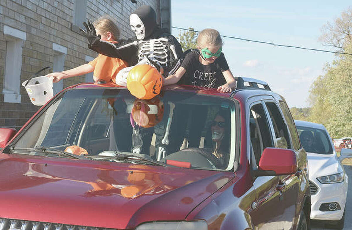 Brooklyn Walker (left), 10, Jace Kroush, 11, and Hadley Walker, 7, collect candy during the WJVO/WJIL Safe Halloween event Thursday. The annual bash is usually indoors, but was changed to drive-through trick-or-treating because of pandemic guidelines.