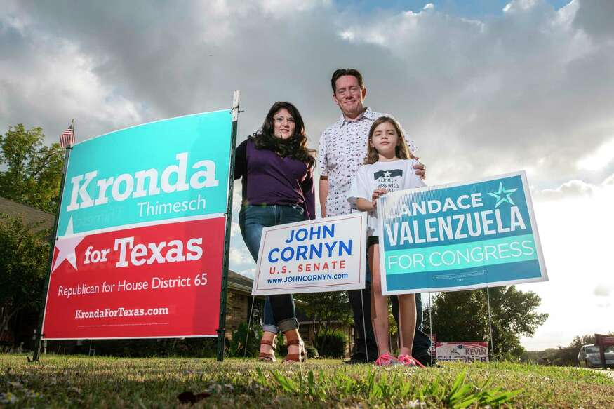 Liz Castaneda, left, her daughter Evelyn Castaneda, 9, and husband Roland Castaneda, with a variety of campaign signs outside their home in Carrollton, Texas, on Thursday, Oct. 22, 2020.