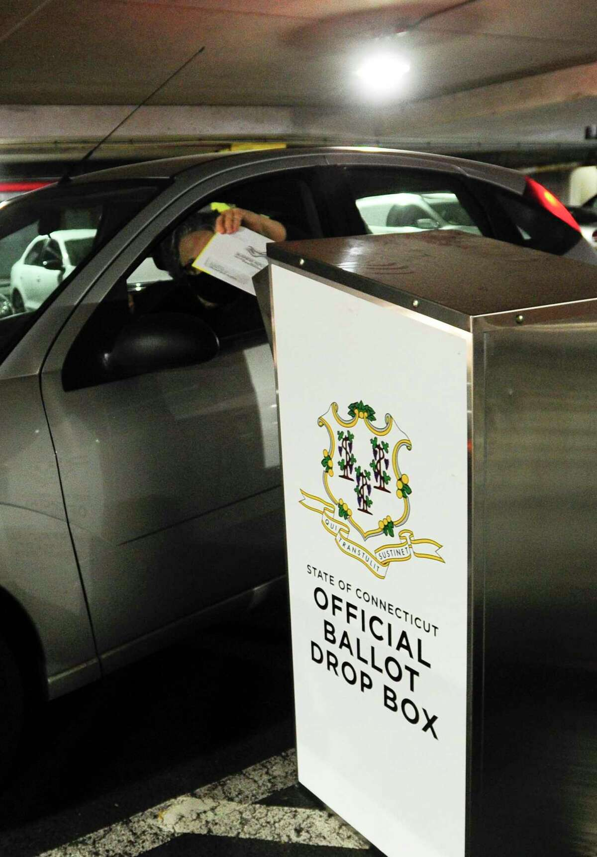 A resident deposits an absentee ballot in an Official Ballot Drop Box at the Stamford Government Center on August 11, 2020 in Stamford, Connecticut.