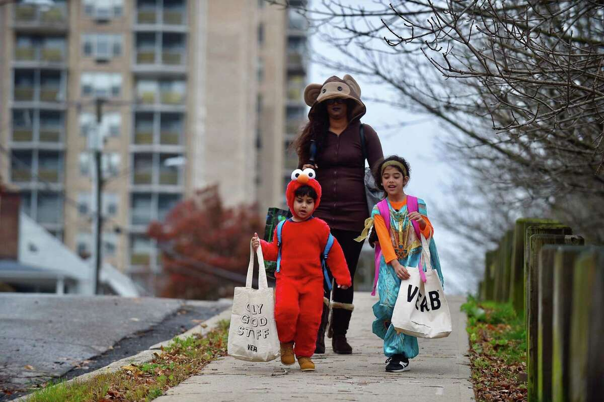 Avani Rampersad of Stamford walks with her children Mia Enot (Princess Jasmine) and Leo Enot (Elmo) as they canvas their neighborhood on Halloween Oct. 31, 2019 in Stamford, Connecticut looking for Tricks and Treats. The decision is based on guidance from Health Director Dr. Jennifer Calder, Martin said in an announcement. Trick-or-treating of any kind involves contact with individuals outside the household and so presents a risk of spreading coronavirus, the mayor said. Calder said trunk-or-treating among cars parked in a lot and other socially distanced alternatives are not safe now.