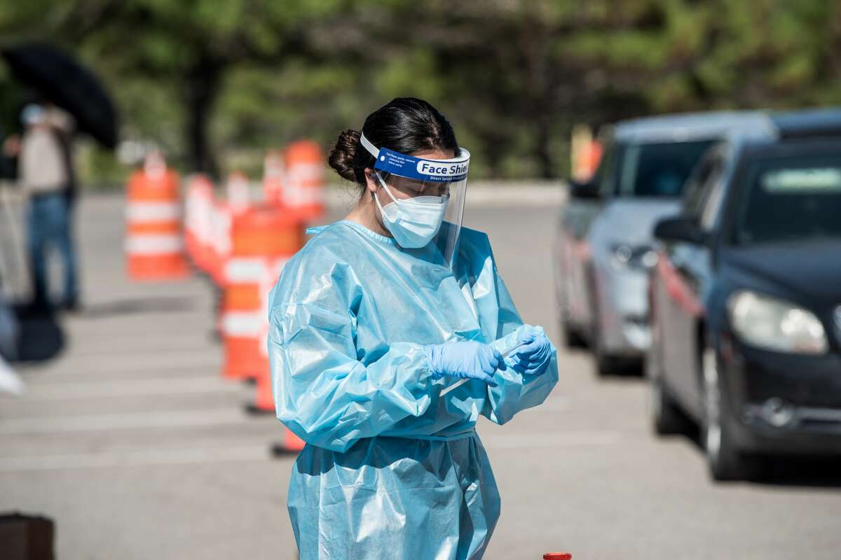 A nurse pulls out a testing swab at a drive-thru site at El Paso Community College Valle Verde campus on July 21, 2020 in El Paso, Texas.
