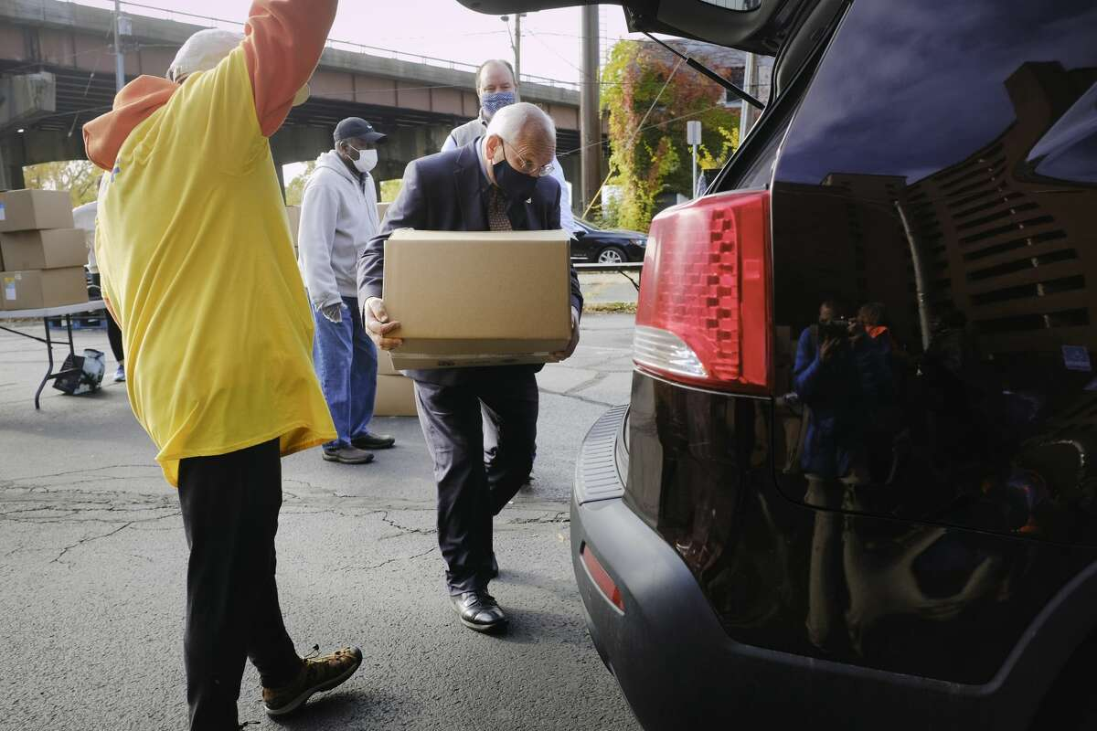 Congressman Paul Tonko loads a food box into a car as he helped out with other volunteers during a food distribution event put on by Catholic Charities of the Diocese of Albany and the Regional Food Bank of Northeastern New York on Wednesday, Oct. 21, 2020, in Albany, N.Y. (Paul Buckowski/Times Union)
