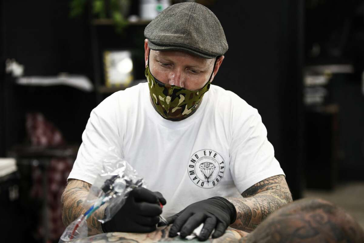 Tattoo artist Kenno works with a client in his store Diamond Eye Tattoo on September 17, 2020.(Photo by Daniel Pockett/Getty Images)