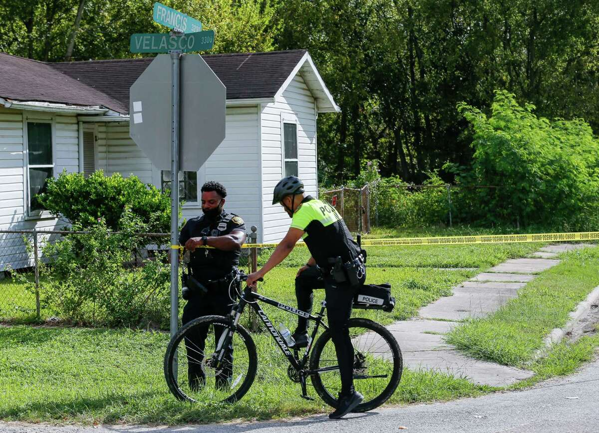 A Houston Police officer takes down crime tape from a scene where a dead body was found, on 3200 block of Francis Street, Friday, Oct. 23, 2020, in Houston.