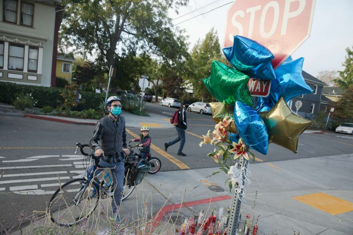 Booth Haley and his son Meru stop by a memorial for Sereinat'e Henderson on Prince Street in Berkeley, Calif. on Oct. 23, 2020.