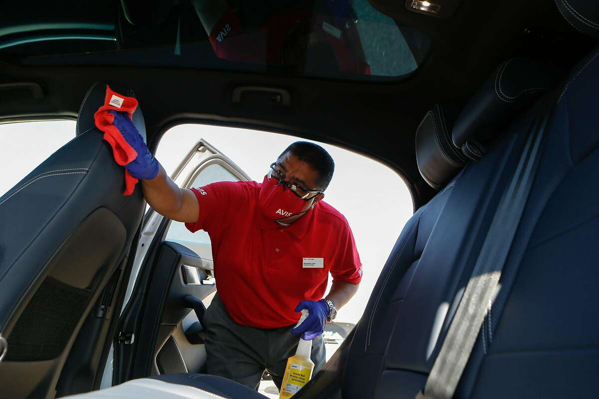 Armando Cruz sanitizes the inside of a Jaguar I-Pace after its test drive at Waymo's temporary location on Tuesday, October 20, 2020 in South San Francisco, Calif. Waymo is ramping up testing of its autonomous cars while including extra sanitizing precautions after each test drive at its temporary base.