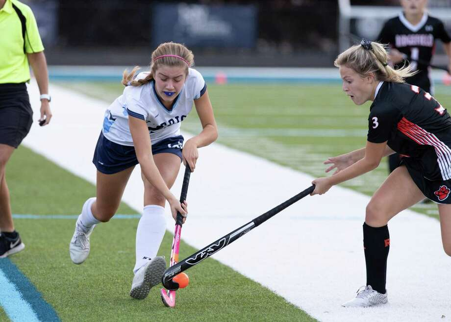 Tishy Cacciapaglia, right, looks to take the ball away from a Wilton player during a recent field hockey game. Photo: Gretchen McMahon / For Hearst Connecticut Media / (C)GretchenMcMahonPhotography