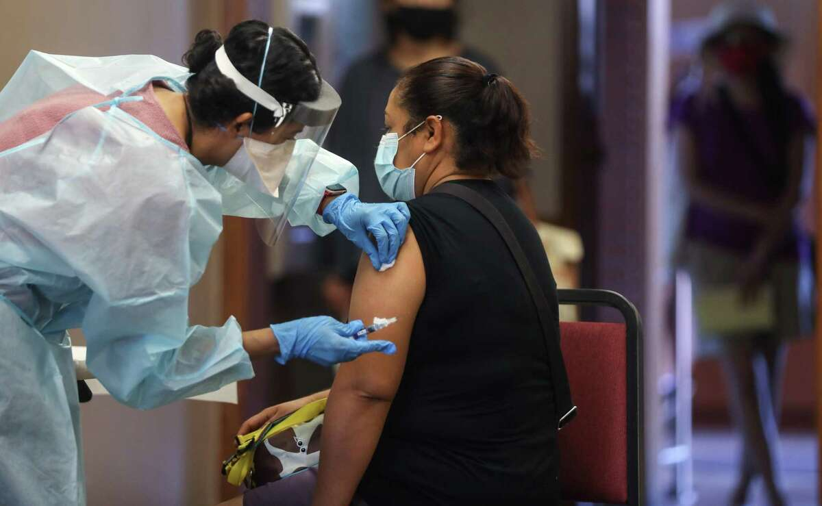LAKEWOOD, CALIFORNIA - OCTOBER 14: A nurse prepares to administer a flu vaccination shot to a woman at a free clinic held at a local library on October 14, 2020 in Lakewood, California. Medical experts are hoping the flu shot this year will help prevent a 'twindemic'- an epidemic of influenza paired with a second wave of COVID-19 which could lead to overwhelmed hospitals amid the coronavirus pandemic. (Photo by Mario Tama/Getty Images)