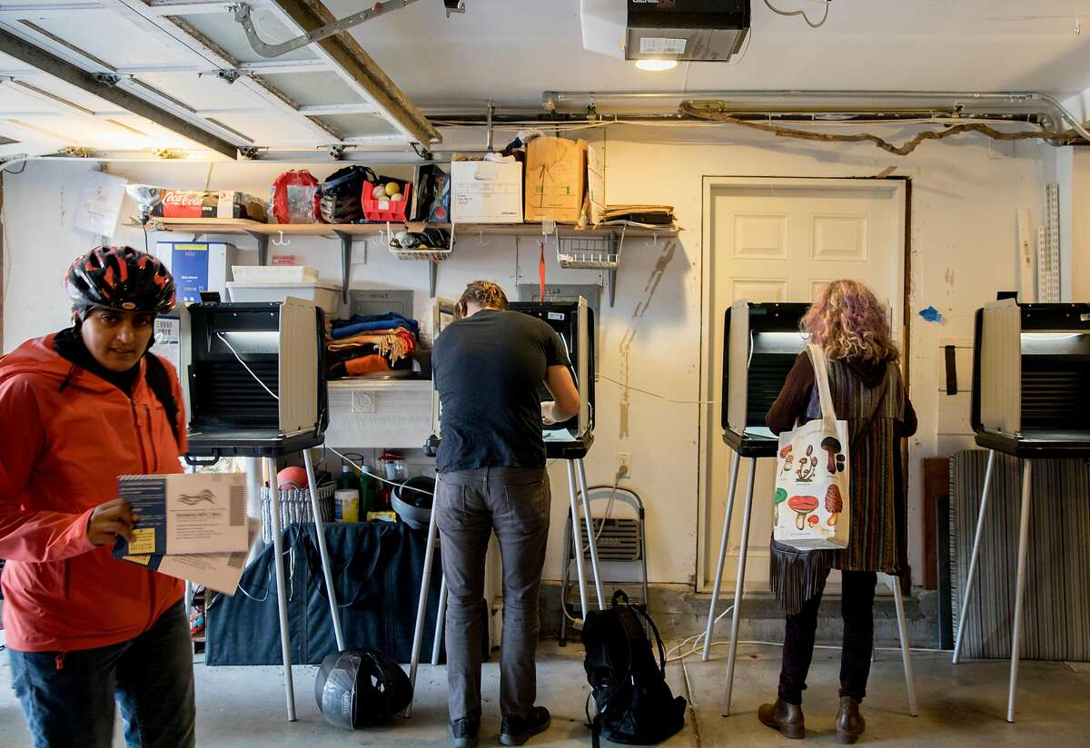 S.F. voters cast their ballots inside a garage polling place along Page Street in 2019. Garage voting is a time-honored S.F. tradition.