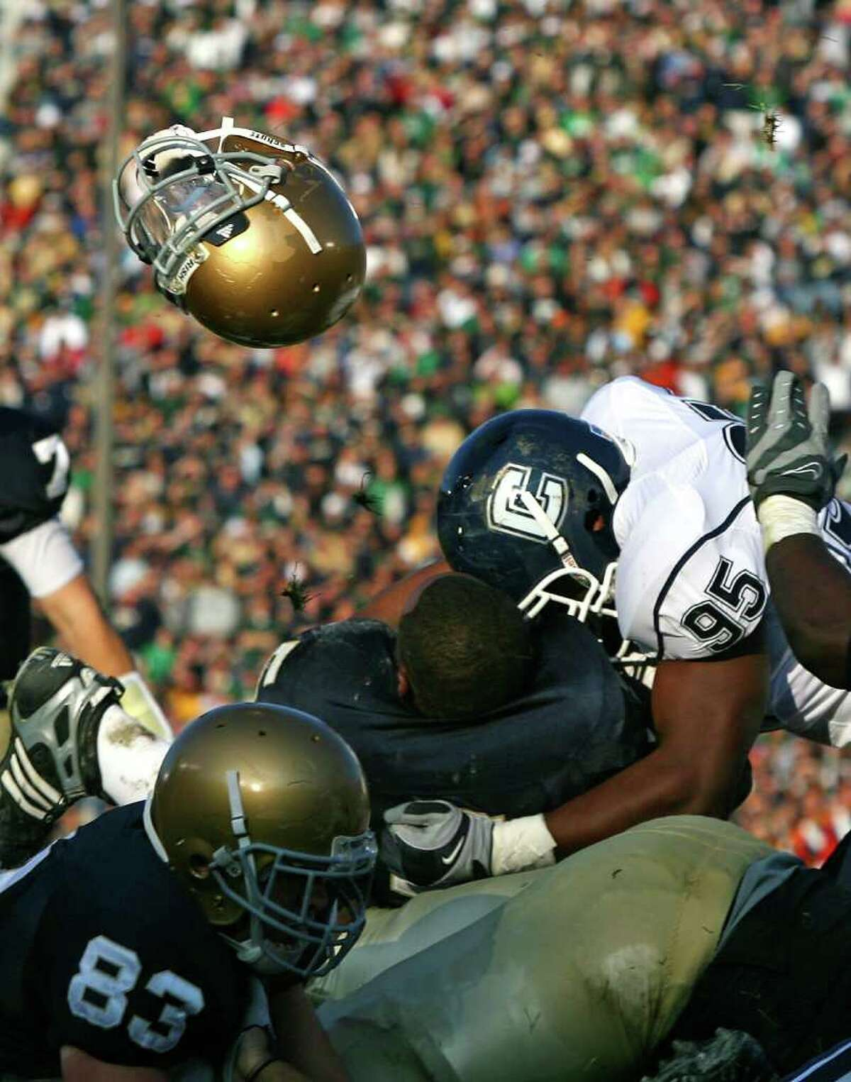 SOUTH BEND, IN - NOVEMBER 21: Armando Allen #5 of the Notre Dame Fighting Irish looses his helmut as he is hit at the goalline by Greg Lloyd #95 of the Univeristy of Connecticut Huskies at Notre Dame Stadium on November 21, 2009 in South Bend, Indiana. (Photo by Jonathan Daniel/Getty Images) *** Local Caption *** Armando Allen;Greg Lloyd