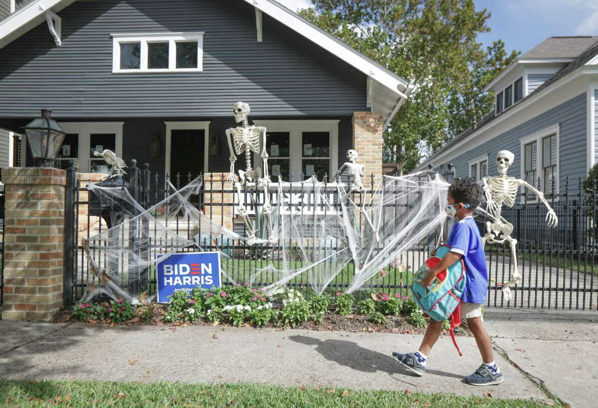 Children and adults walk pass a Halloween decorated home on Harvard near E. 10th Street Thursday, Oct. 22, 2020, in Houston.
