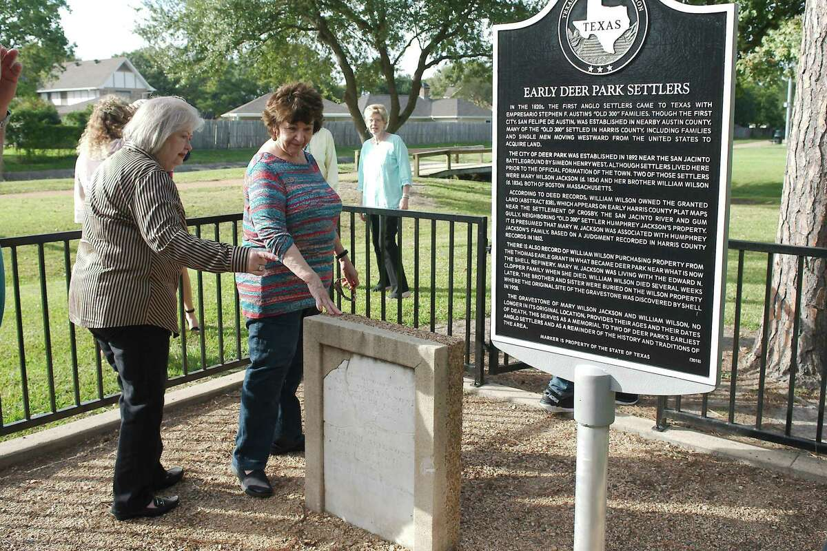 Deer Park Historical Committee members Janet Horsch and Pat Adams view the headstone and historical marker set in memory of early Deer Park residents Mary W. Jackson and William Wilson during a dedication ceremony Tuesday at Dow Park.