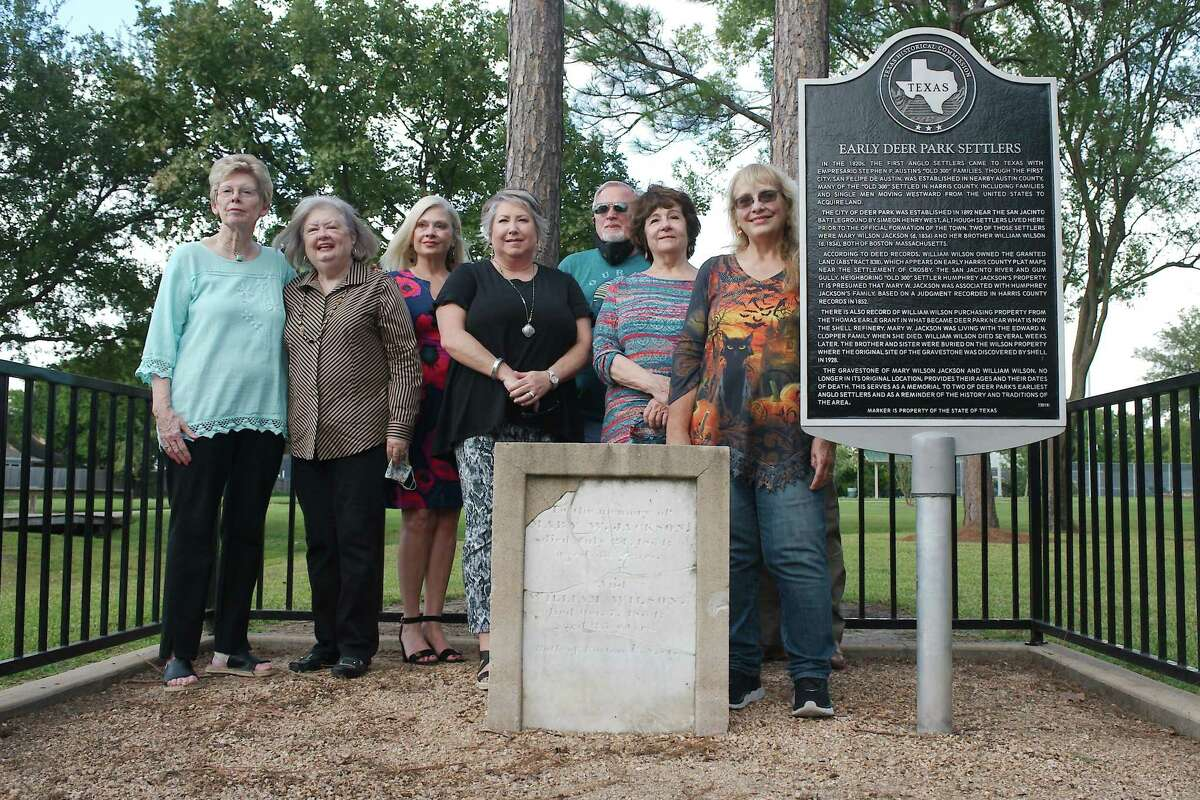 Members of the Deer Park Historical Committee stand by a historical marker and headstone set in memory of early Deer Park residents Mary W. Jackson and William Wilson during a dedication ceremony Tuesday at Dow Park.