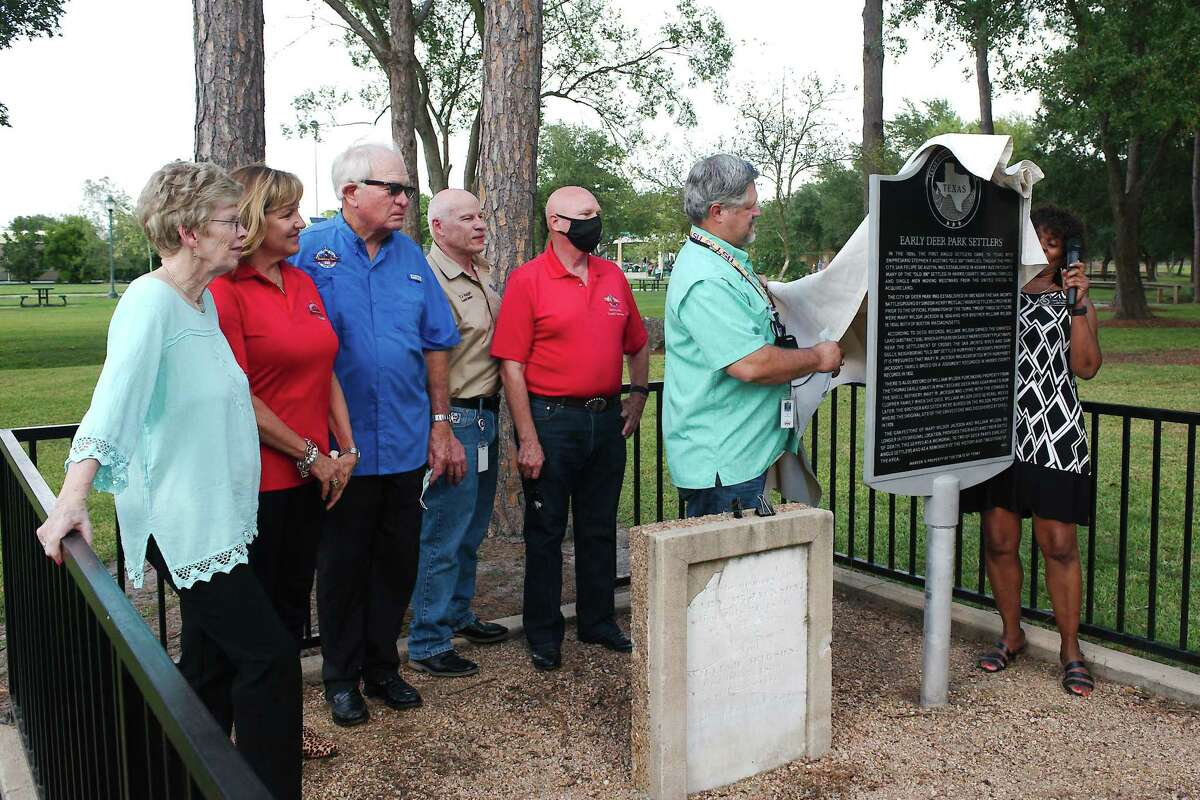 Members of the Deer Park City Council watch as Mayor Jerry Mouton and Harris County Historical Commission Marker Dedication Chairman Debra Blacklocl-Sloan unveil a historical marker set in memory of early Deer Park residents Mary W. Jackson and William Wilson during a dedication ceremony Tuesday at Dow Park.