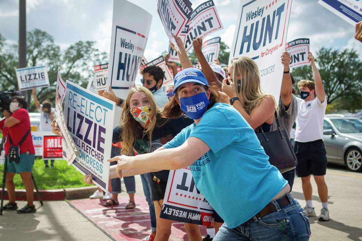 Campaign volunteers for candidates Wesley Hunt and Lizzie Pannill Fletcher compete for space outside of the early voting location at Houston Community College on Wednesday.