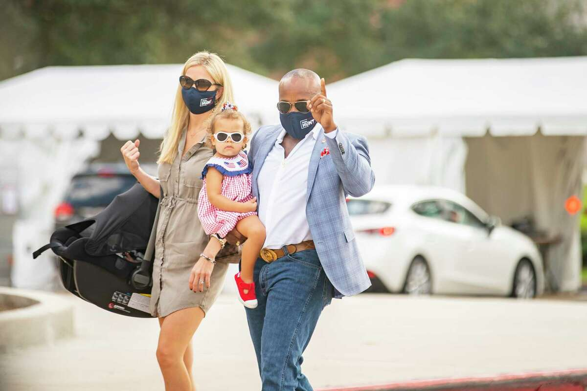 Congressional candidate Wesley Hunt waves to his supporters as he walks in to early vote at Houston Community College West Loop Campus with his wife, Emily, and daughters Victoria and Olivia, Wednesday, Oct. 21, 2020, in Houston.