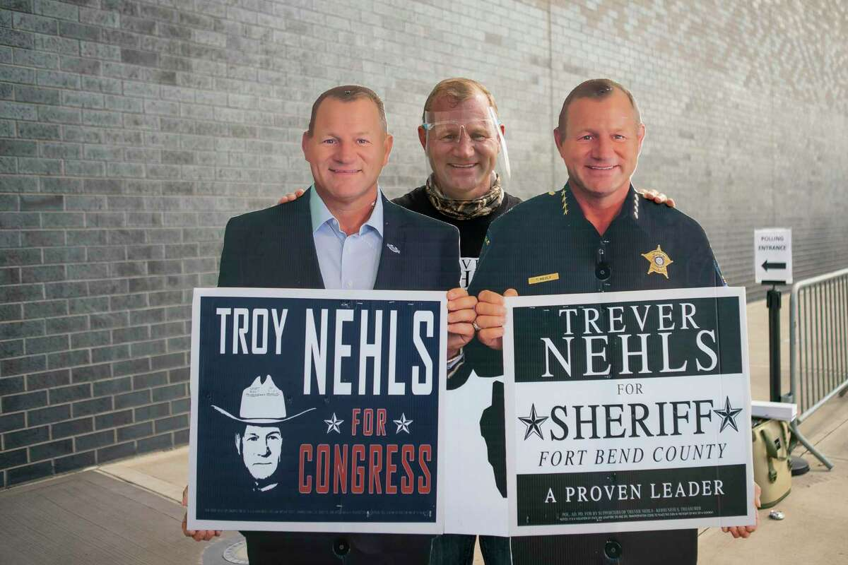 Fort Bend sheriff candidate Trevor Nehls campaigns outside of the early voting center with cardboard cutouts of himself and his twin brother, Republican congressional candidate Troy Nehls, at the Smart Financial Center, Wednesday, Oct. 21, 2020, in Sugar Land.