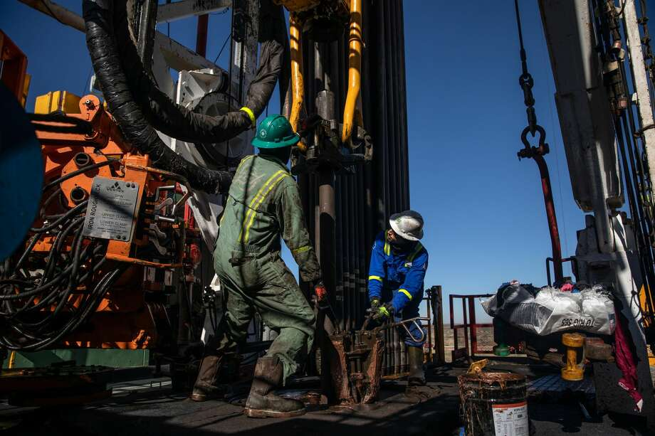 Floorhands work on a drilling rig contracted to Shell near Wink in this file photo. Oil edged lower with growing virus restrictions and signs the labor-market recovery may be slowing in the U.S. dampens the near-term demand outlook. Photo: TAMIR KALIFA/NYT