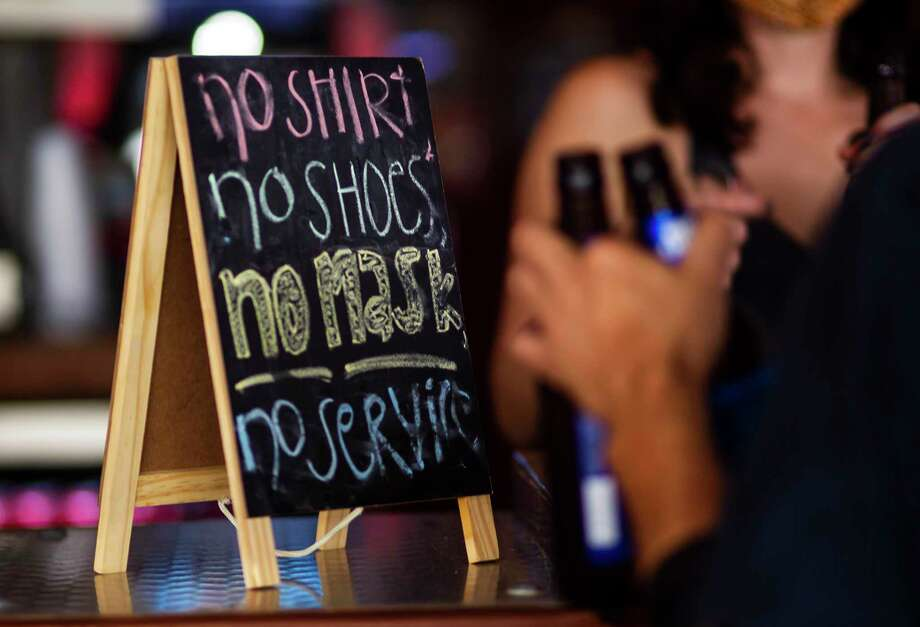 A sign on the bar at the West Alabama Ice House reminds patrons that they need a mask to be served, Saturday, Oct. 3, 2020, in Houston. Photo: Mark Mulligan, Houston Chronicle / Staff Photographer / © 2020 Mark Mulligan / Houston Chronicle