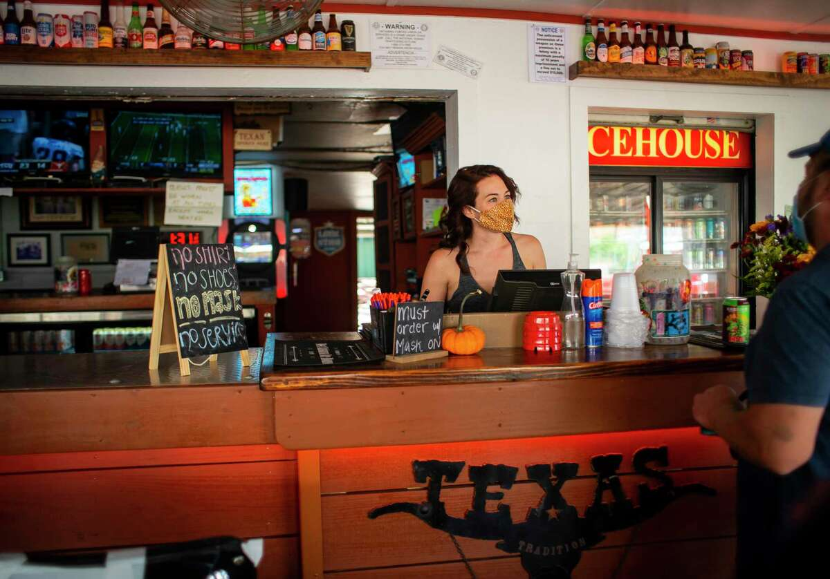 Bartender Randi Null serves a patron at the West Alabama Ice House on Saturday, Oct. 3, 2020, in Houston.