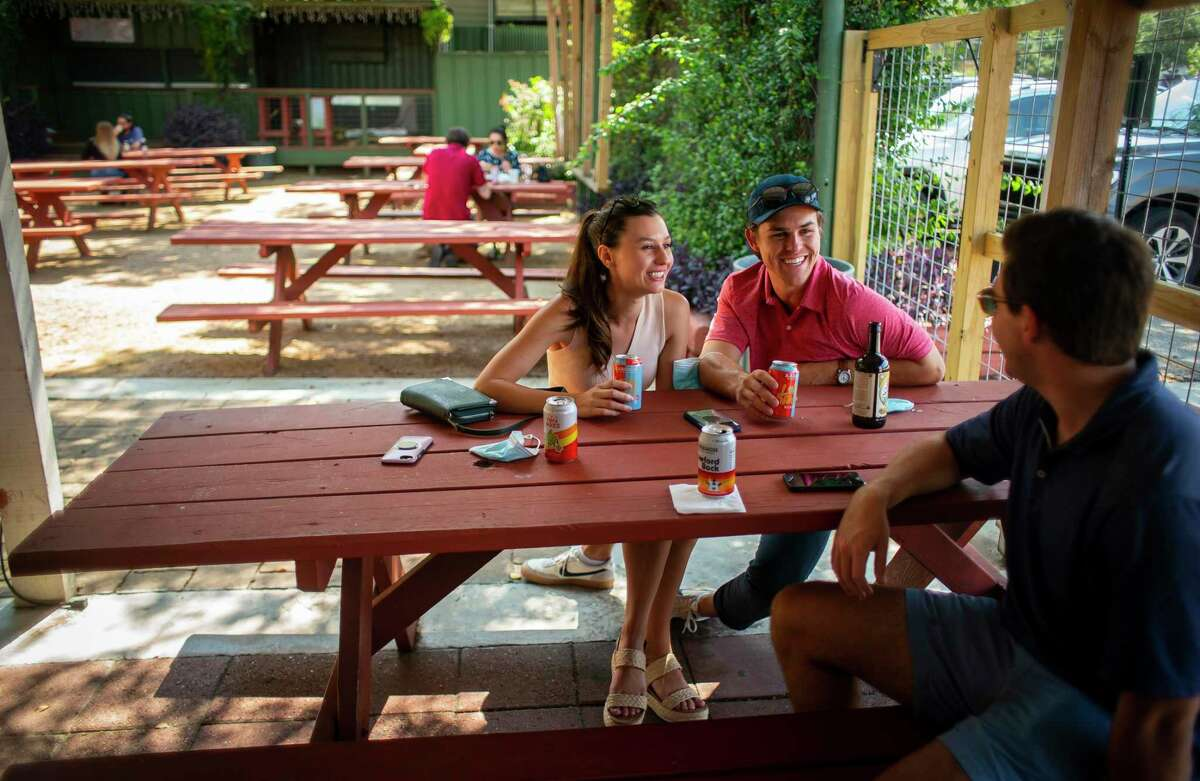 Maddie Drake (left) and and Harrison Harp talk with MG Jadick at the West Alabama Ice House, Saturday, Oct. 3, 2020, in Houston. They said they have been preferring outdoor, beer garden style spaces like the ice house since bars began reopening during the Covid-19 pandemic.