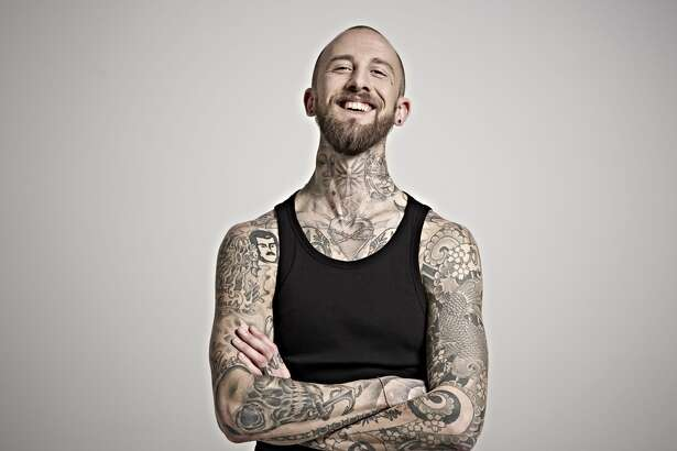 Portrait of bearded man with tattooed chest, neck and arms smiling confidently to camera.