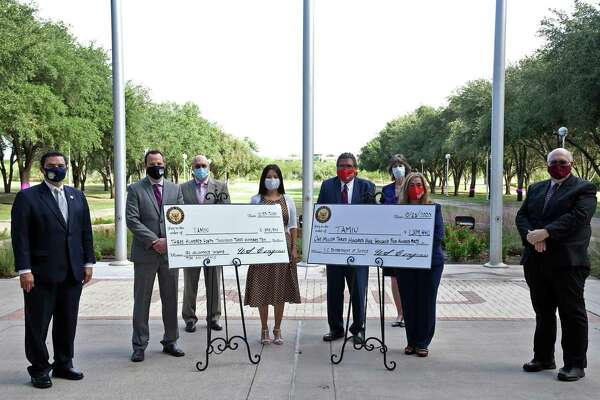 The TAMIU staff in charge of the VITA, TRIO STEM and grant writing pose with Dr. Pablo Arenaz and Congressman Henry Cuellar after the $1.6 million grants were presented.