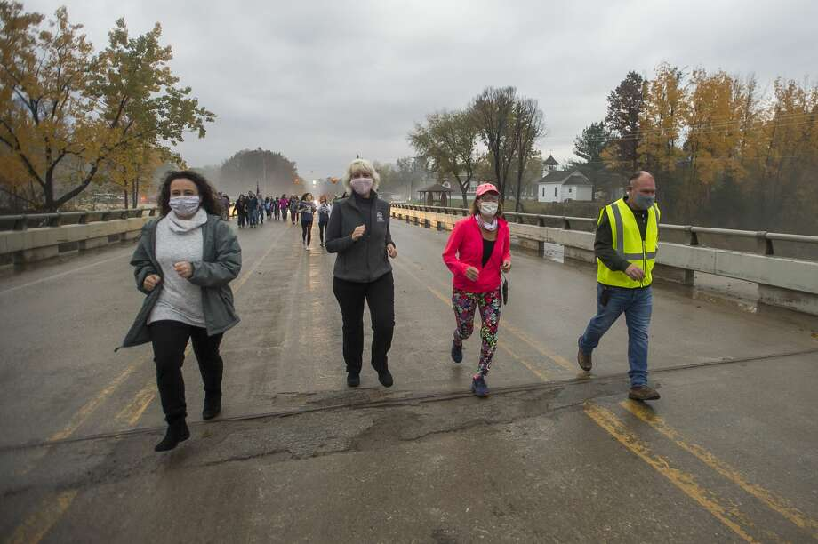 From left, Midland County Commissioner Jeannette Snyder, State Rep. Annette Glenn, Sanford Village President Dolores Porte and Malley Construction Owner Brad Malley jog across the newly reconstructed Saginaw Road Bridge as it is officially reopened for the first time after being destroyed due to the May dam failures and flooding, on Oct. 23, 2020 in Sanford. (Katy Kildee/kkildee@mdn.net) Photo: (Katy Kildee/kkildee@mdn.net)