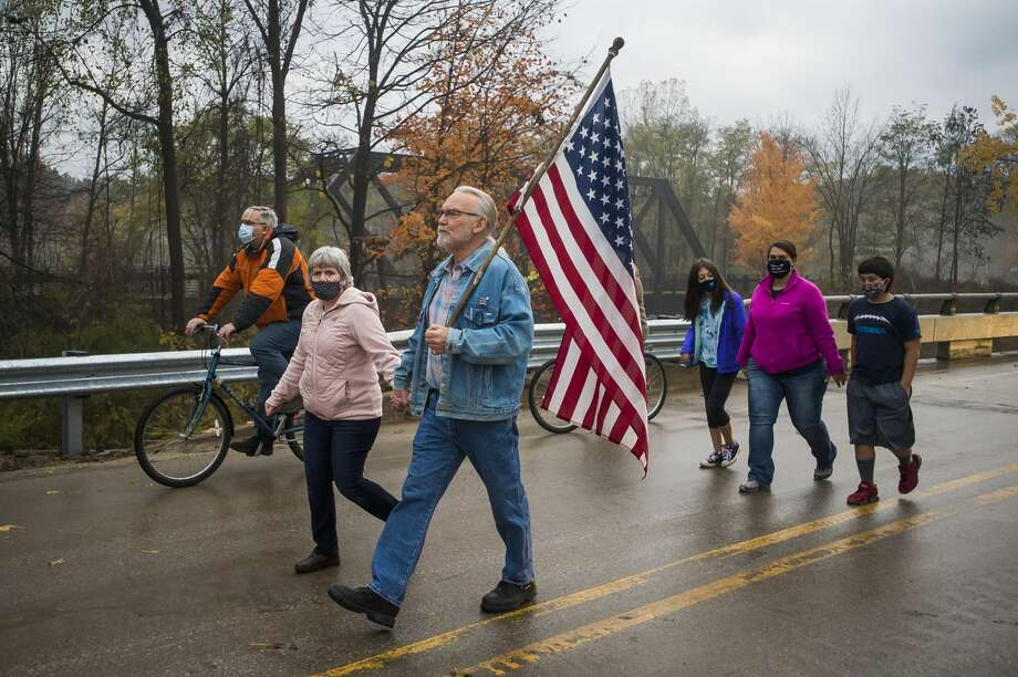 Ed and Cheryl Crandell of Sanford, center, cross the newly reconstructed Saginaw Road Bridge as it is officially reopened, for the first time after being destroyed during the May dam failures and flooding, alongside community leaders and residents Friday morning, Oct. 23, 2020 in Sanford. (Katy Kildee/kkildee@mdn.net) Photo: (Katy Kildee/kkildee@mdn.net)