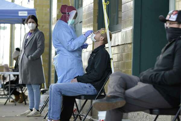 A medical staff member performs a Covid-19 test outside the Family Healthcare building in downtown Fargo, North Dakota, U.S., on Thursday, Oct. 15, 2020. The North Dakota Department of Health on Thursday, Oct. 15, reported five deaths from COVID-19 and another record-high number of active cases. Photographer: Dan Koeck/Bloomberg