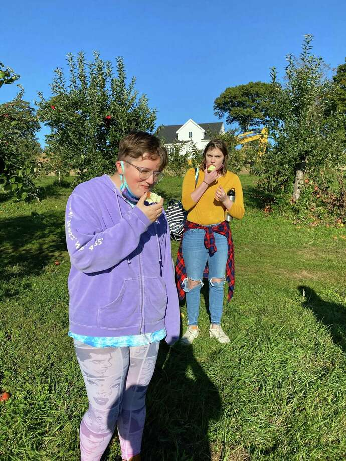 Glenholme students Tia G. and Erika F. stop apple picking for a moment to sample the goods. Photo: Contributed Photo /