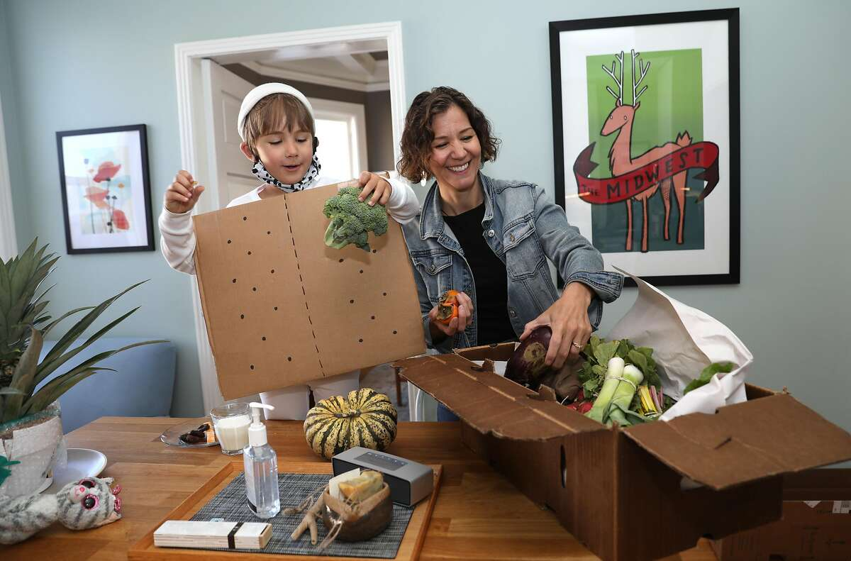 Luca Vinocour (left), dressed as a s'more checks out a vegetable delivery with his mom Jessica.