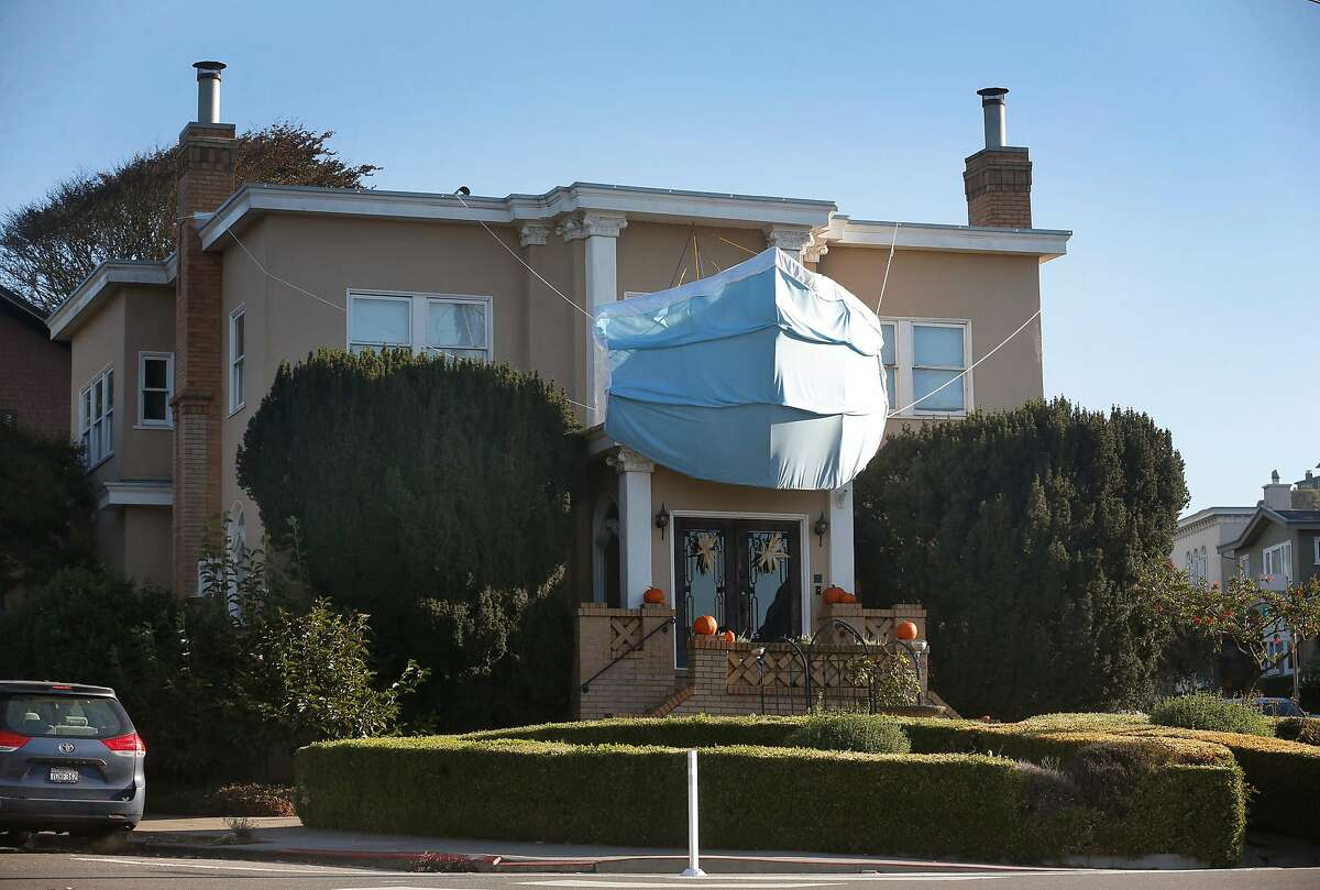 As a sign of the times, a West Portal home is decked out for Halloween with a giant face mask in San Francisco, Calif. on Tuesday, Oct. 20, 2020.