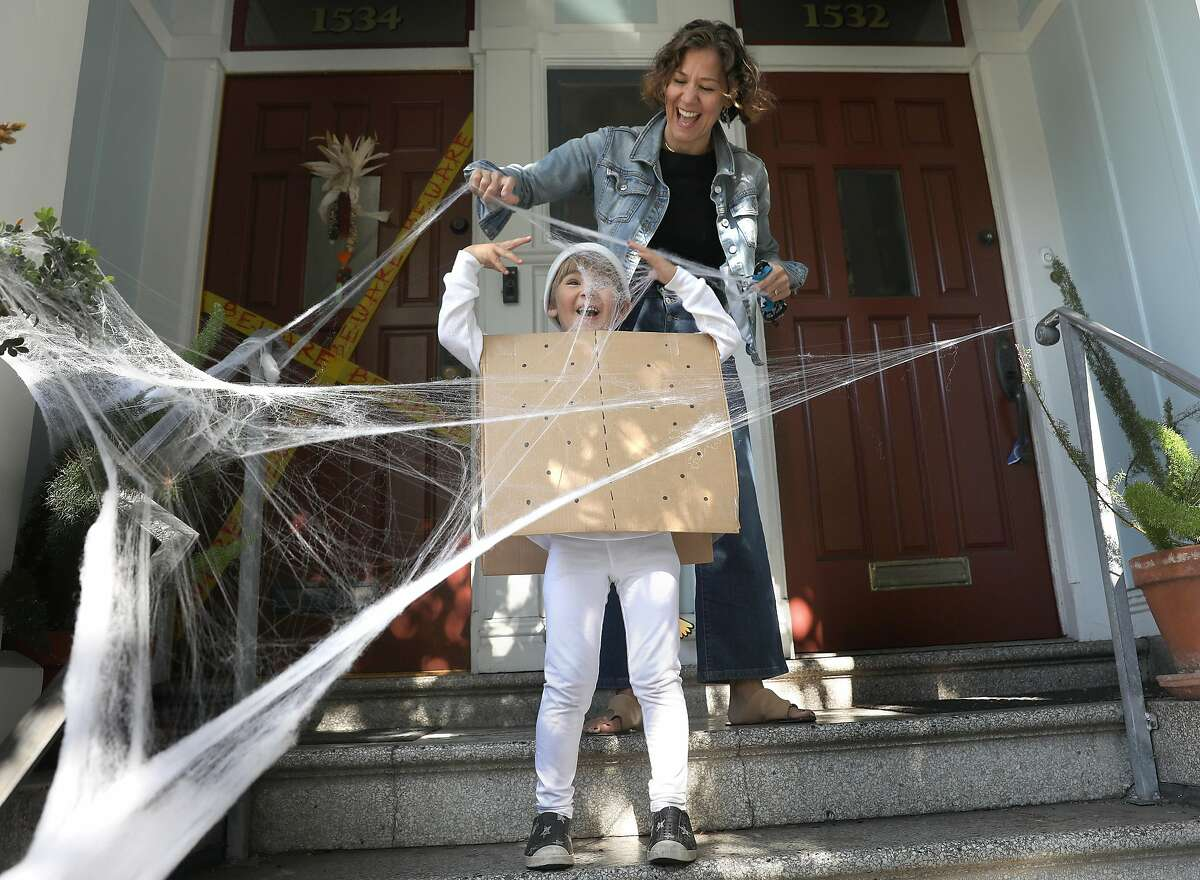Jessica and her 5-year-old son Luca Vinocour play with spider web as they decorate the house in San Francisco.