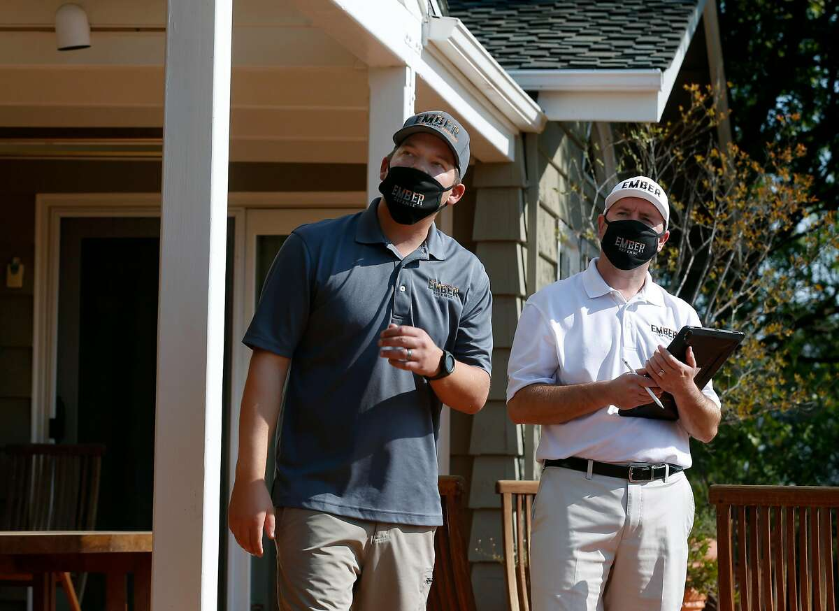 Devan LeBlanc (left) and Adam Iveson, co-founders of Ember Defense, describe wildfire prevention measures to a homeowner in Portola Valley.