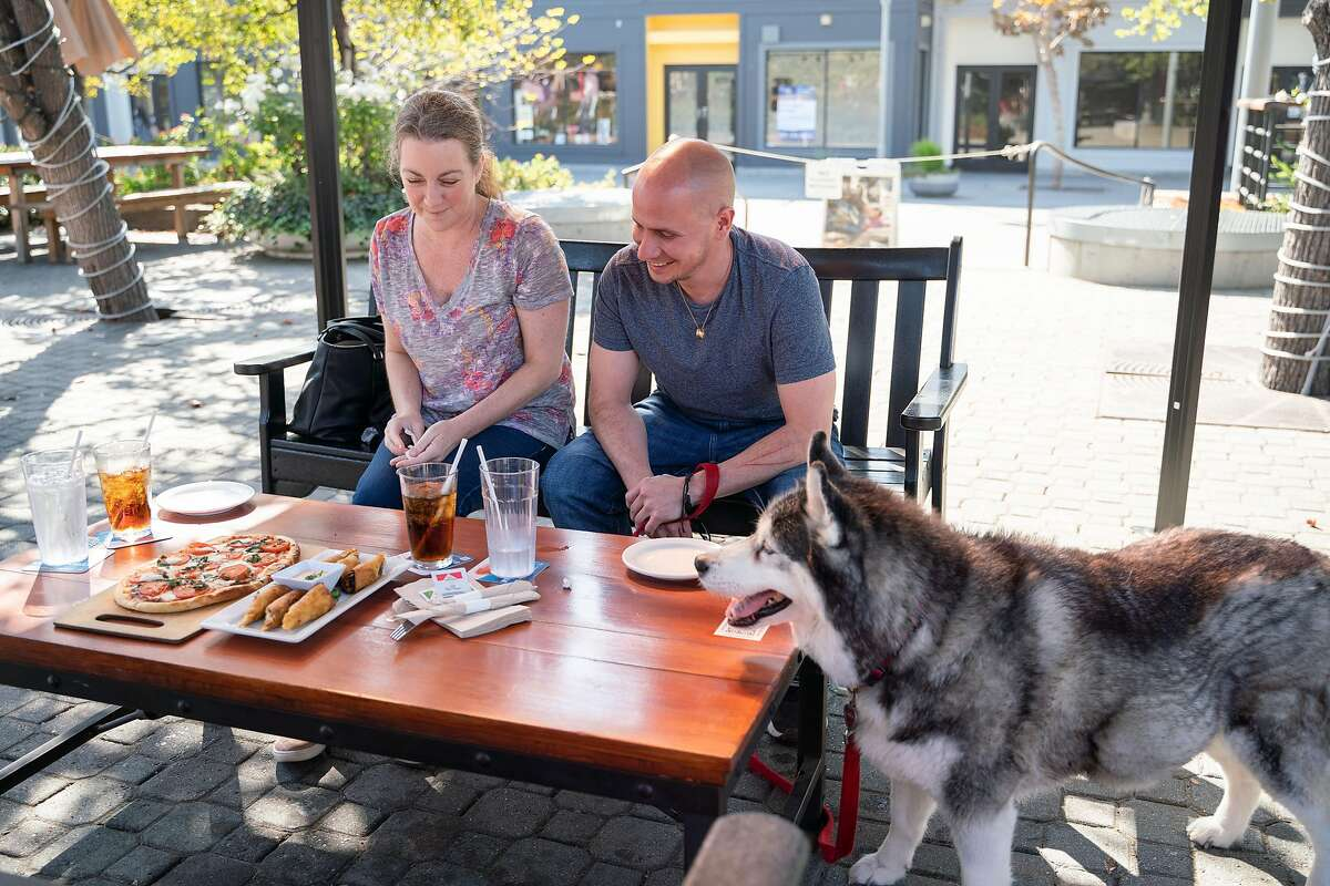 Jessica McGuire (left) Peter Manning and their dog Kayla eat lunch at Plank in Oakland on Friday.