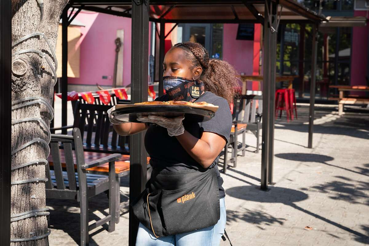 Waitress Asia Banks of Oakland serves customers at Plank. The restaurant expanded service indoors Friday for the first time since shelter-in-place was imposed.