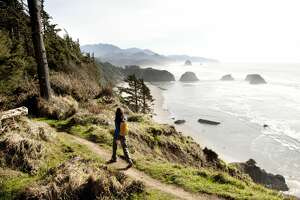 A woman hiking a secluded path along the coastline.