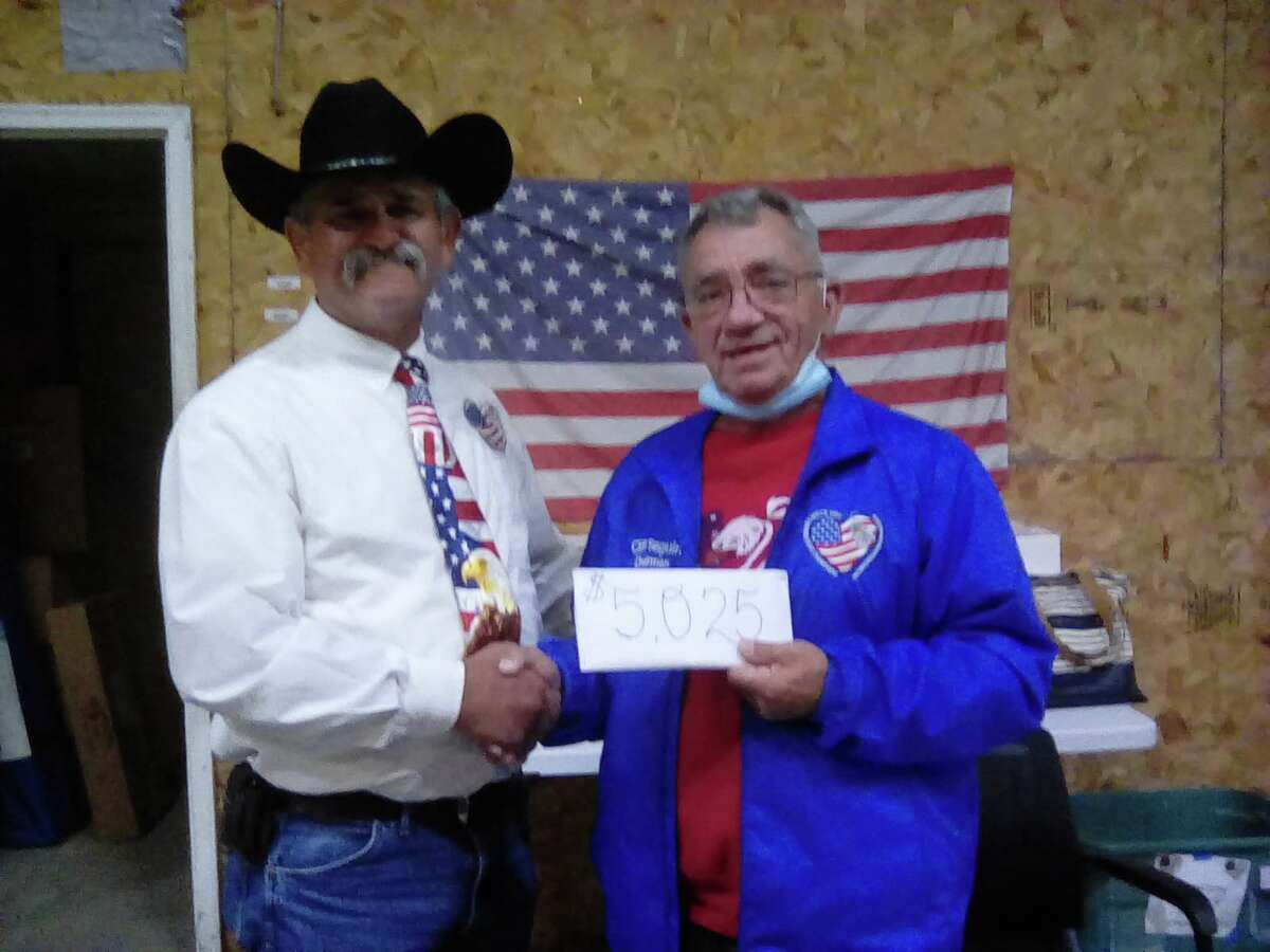 Country musician and singer Phil Hoyt presents $5,025 he raised to Cliff Seguin, founder of Operation Adopt A Soldier, at the charity's office in Wilton., N.Y. (Provided photo)