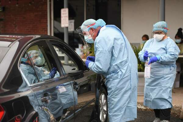 Dentist Tom McManus and dental hygienist Ana Dacosta administer a Covid-19 swab test outside the Commuinity Health Center of Danbury on Delay Street in Danbury on Oct. 13.