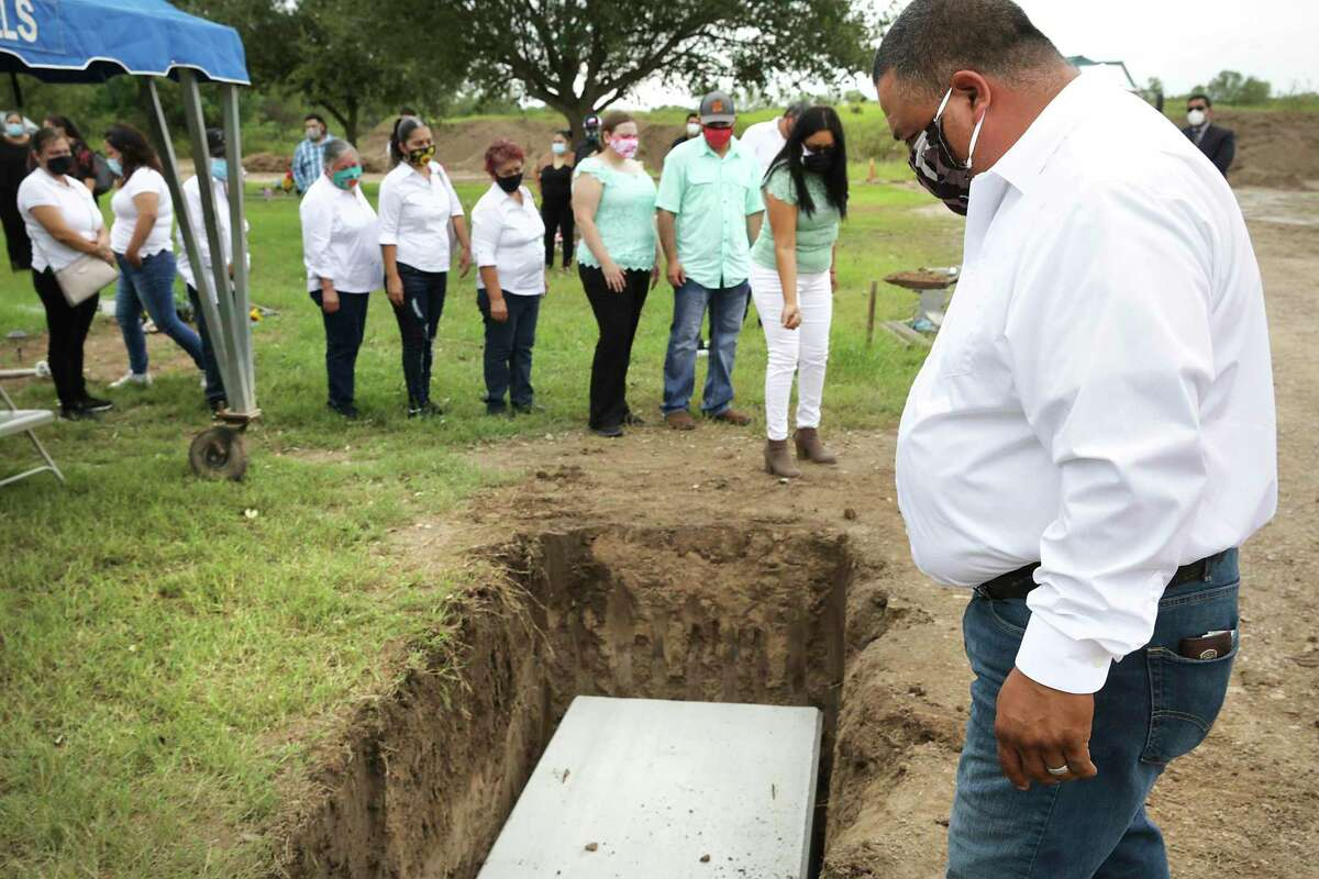Francisco Romero looks in the grave of his mother Ninfa Romero, who died of COVID-19, as she is buried July 29 by her family at Garden of Angels Cemetery in Mission.