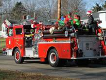 File photo of members of the Hilltop Hose Company of the Ansonia Fire Department driving around the local neighborhoods, spreading holiday cheer and handing out popcorn balls.